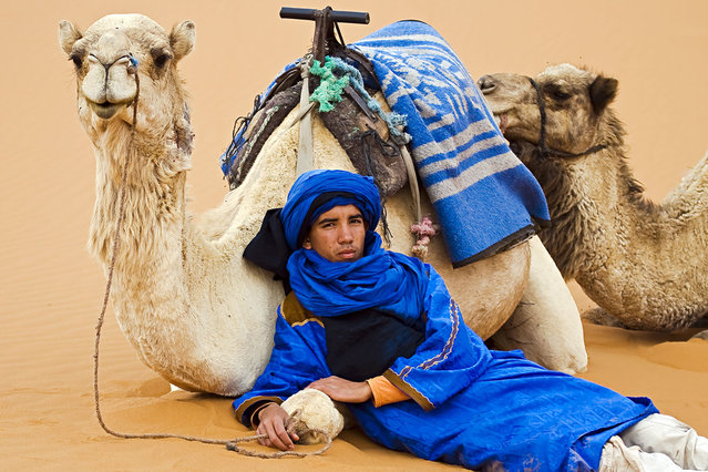 """""""Hassan and his Camels"""". While photographing the sunset in the Sahara Desert, I turned around to see Hassan and his camels patiently waiting to take the group back to base camp. Location: The Sahara Desert, near Merzouga, Moroccco. (Photo and caption by Jack Wickes/National Geographic Traveler Photo Contest)"""