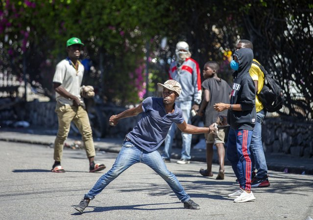 A demonstrator throws rocks at the police during a protest to demand the resignation of Haitian President Jovenel Moise in Port-au-Prince, Haiti, Sunday, February 7, 2021. (Photo by Dieu Nalio Chery/AP Photo)