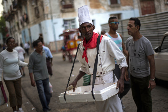 In this January 17, 2015, photo, Yurien Rojas, who sells custard filled pastries known as Señoritas, waits for customers on a street in Havana, Cuba. (Photo by Ramon Espinosa/AP Photo)