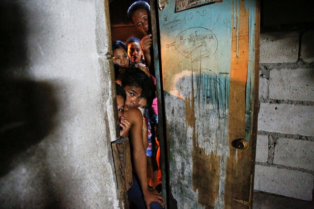 People peek inside a house in which five people were killed in Manila, Philippines early November 1, 2016. (Photo by Damir Sagolj/Reuters)