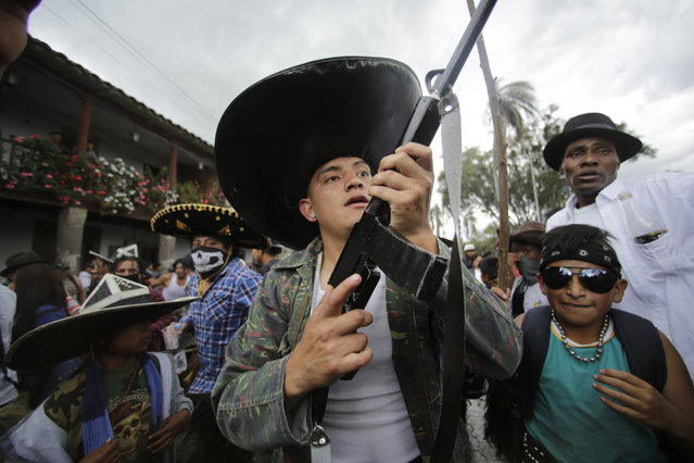 Indigenous men in costume, one holding a mock gun made of wood, dance to the rhythm of the monotonous tune of San Juanito, as groups from different communities compete to occupy the main plaza during the Sun Festival in Cotacachi, Ecuador, Sunday, June 24, 2018. (Photo by Dolores Ochoa/AP Photo)