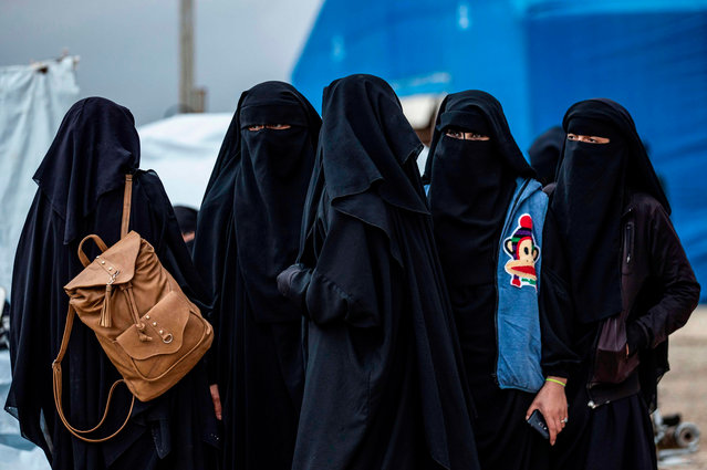 Syrian women get ready to leave the Kurdish-run al-Hol camp holding relatives of alleged Islamic State (IS) group fighters, in the al-Hasakeh governorate in northeastern Syria, on November 16, 2020. A Kurdish official in charge of the region's camps, said 515 people from 120 families were returning to areas in the east of Deir Ezzor province, the first to do so after the Kurdish authorities in northeast Syria vowed to allow thousands of Syrians including the families of IS fighters out of the over-populated camp. (Photo by Delil Souleiman/AFP Photo)