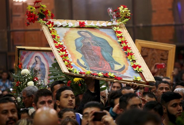 Pilgrims hold up images of the Virgin of Guadalupe during an annual pilgrimage in honor of the Virgin, the patron saint of Mexican Catholics, at the Cathedral of Ciudad Juarez, Mexico December 12, 2015. (Photo by Jose Luis Gonzalez/Reuters)