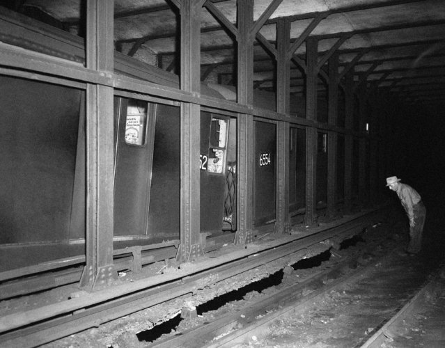 Two cars of the Lexington Avenue subway train were caught on collapsing tracks in the Astor Place station, July 15, 1956.  The tracks collapsed as a result of seepage from the more than 100,000 gallons of water poured on the fire in the old Wanamaker department store in New York. (Photo by AP Photo)