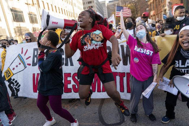 Shaqualla Johnson, holding bullhorn, jumps during a march celebrating the election of Joe Biden as president in Detroit, Saturday, November 7, 2020. (Photo by David Goldman/AP Photo)