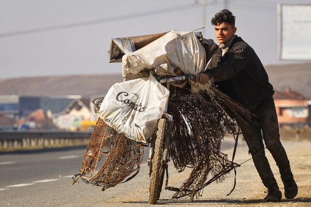 A Roma boy pushes his bicycle filled with iron scrap near the town of Obilic, Kosovo, 05 February 2021. (Photo by Valdrin Xhemaj/EPA/EFE)