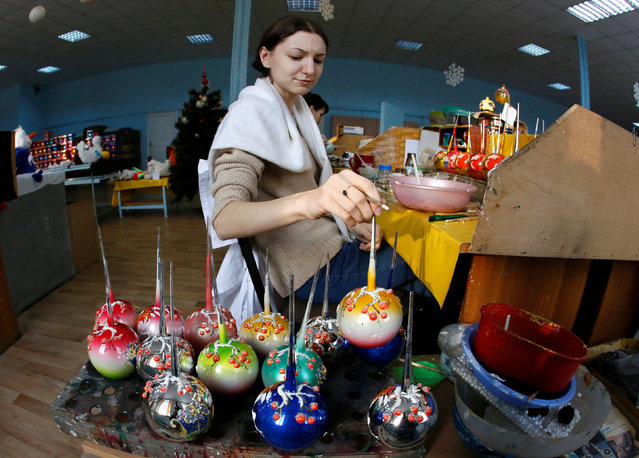 """An employee holds a newly painted glass Christmas and New Year decoration at the """"Biryusinka"""" toy factory, which has been producing decorations and toys for the festive season since 1942, in the Siberian city of Krasnoyarsk, Russia, November 16, 2016. (Photo by Ilya Naymushin/Reuters)"""