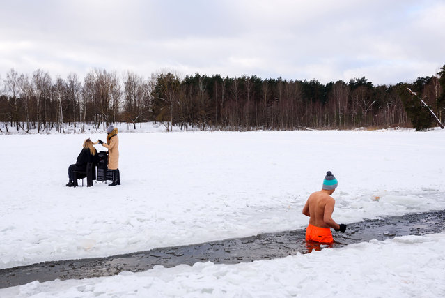 An hairdresser cuts hair on the frozen lake Babelitis while a winter swimmer go swimming in an ice hole on February 15, 2021, in Riga, Latvia, as hairdressers are not allowed to work due to the new coronavirus COVID-19 pandemic. (Photo by Gints Ivuskans/AFP Photo)