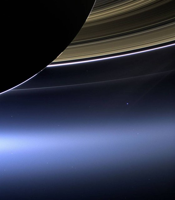 Handout photo issued by NASA of the Earth appearing as a pale blue dot below Saturn's majestic rings in this stunning image from the American space agency Nasa's Cassini spacecraft. Taken on July 19 using Cassini's wide angle camera, it shows how the Earth appears from a distance of 900 million miles. The other fainter dots nearby are stars. (Photo by NASA/JPL-Caltech/Space Science Institute)