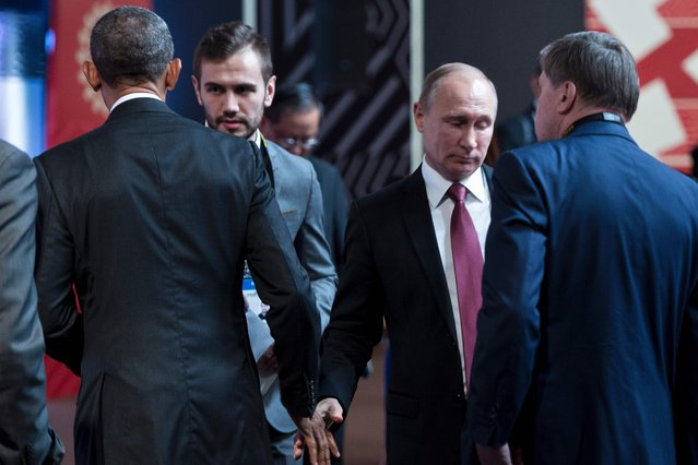 US President Barack Obama (L) and Russia' s President Vladimir Putin (2R) walk from each other after speaking and shaking hands before an economic leaders meeting at the Asia- Pacific Economic Cooperation Summit at the Lima Convention Centre November 20, 2016 in Lima. (Photo by Brendan Smialowski/AFP Photo)