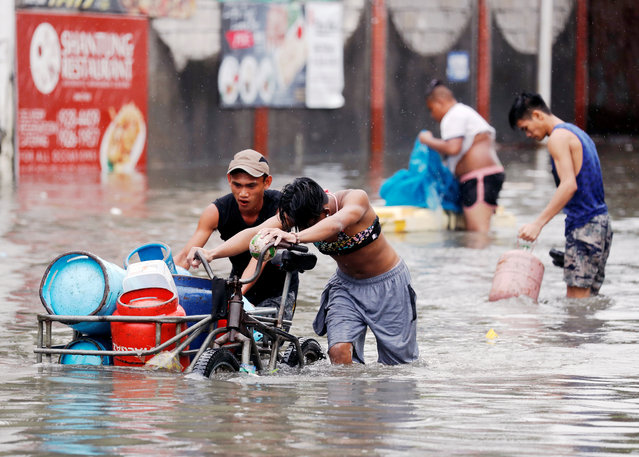 Residents transport LPG containers along a flooded street caused by monsoon rains and Tropical Storm Son-Tinh in Quezon city, Metro Manila, Philippines on July 17, 2018. (Photo by Erik De Castro/Reuters)