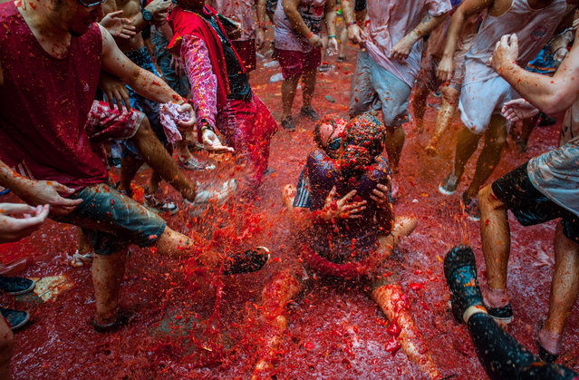 Two Revellers kiss each other covered in tomato pulp while participating the annual Tomatina festival on August 28, 2013 in Bunol, Spain. An estimated 20,000 people threw 130 tons of ripe tomatoes in the world's biggest tomato fight held annually in this Spanish Mediterranean town. (Photo by David Ramos/Getty Images)