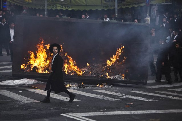 An ultra-Orthodox Jewish boy walks in front of a garbage bin set on fire during a protest in Jerusalem's Mea Shearim neighbourhood, against the jailing of Jewish seminary students who failed to comply with a recruitment order, February 8, 2015. (Photo by Nir Elias/Reuters)