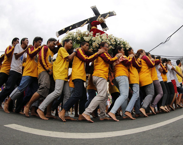 Filipino barefoot Catholics carry a replica of the Black Nazarene during a procession ahead of the Black Nazarene feast day celebrations in Manila, Philippines, 07 January 2016. (Photo by Francis R. Malasig/EPA)