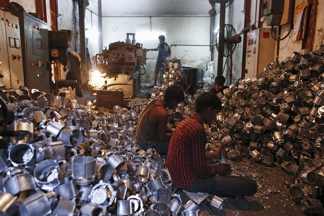 Workers make parts for household mixers at a workshop in Mumbai in this June 3, 2013 file photo. China's factory activity shrank for a 10th straight month in December as surveys across Asia showed industry struggling with slack demand even as the policy cupboard is looking increasingly bare of fresh stimulus. (Photo by Danish Siddiqui/Reuters)