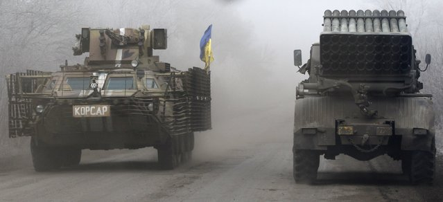Ukrainian military vehicles travel on the road between the towns of Dabeltseve and Artemivsk, Ukraine, Saturday, February 14, 2015. (Photo by Petr David Josek/AP Photo)