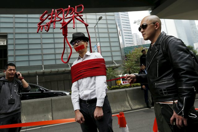 "A local artist ties himself with a rope that forms characters reading ""Kidnap"" during a protest over the disappearance of booksellers, in Hong Kong, China January 10, 2016. (Photo by Tyrone Siu/Reuters)"