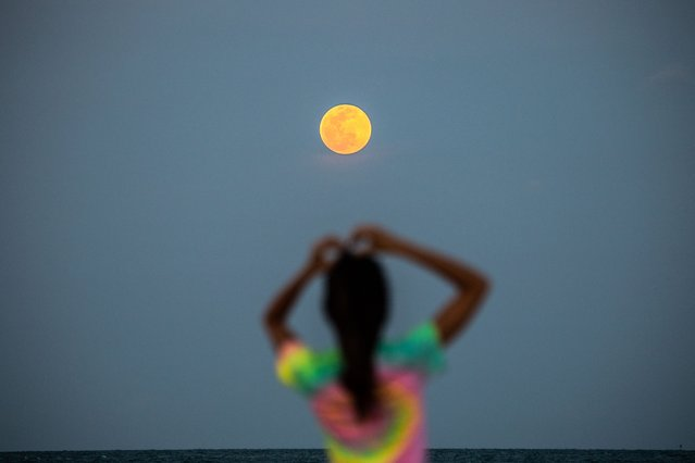 A Super Pink Full Moon is seen in the background as people relax on the beach in Miami Beach, on April 26, 2021. (Photo by Chandan Khanna/AFP Photo)