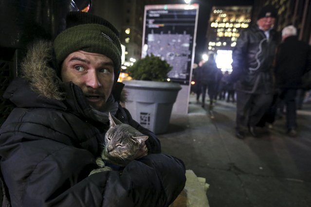 Keith Rosario sits with his cat Storm as he panhandles on the street outside Pennsylvania Station in the Manhattan borough of New York, January 5, 2016. (Photo by Carlo Allegri/Reuters)