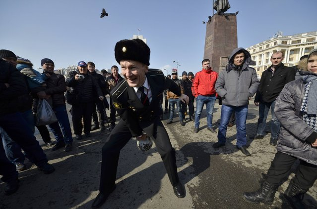 A Russian navy sailor lifts a weight while participating in a competition during celebrations for the Defender of the Fatherland Day in the far eastern city of Vladivostok February 23, 2015. (Photo by Yuri Maltsev/Reuters)