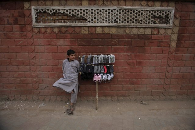 A boy selling masks waits for customers in Peshawar, Pakistan, December 8, 2015. (Photo by Fayyaz Hussain/Reuters)