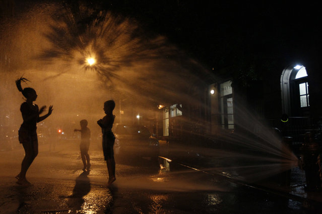 In this July 21, 2011, file photo, Vanity Mendez, 11, left, Isaiah Rivera, 6, center, and Jonathan Medina, 11, cool off at an open fire hydrant in the East Village neighborhood of Manhattan. (Photo by Mary Altaffer/AP Photo)