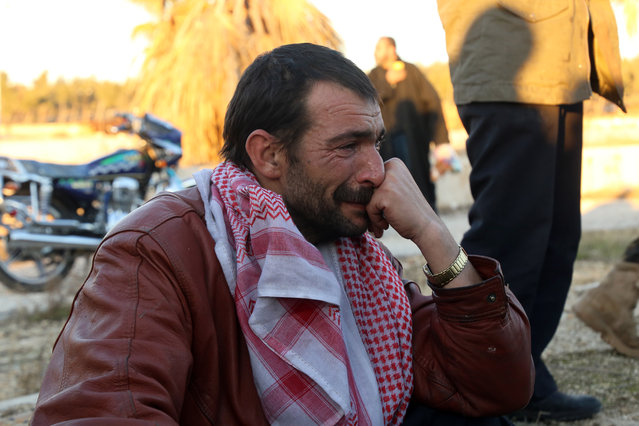 A Syrian man, who was evacuated from rebel-held neighbourhoods in the embattled city of Aleppo, cries upon his arrival in the opposition-controlled Khan al-Aassal region, west of the city, on December 15, 2016, the first stop on their trip, where humanitarian groups will transport the civilians to temporary camps on the outskirts of Idlib and the wounded to field hospitals. Hundreds of civilians and rebels left Aleppo under an evacuation deal that will allow Syria's regime to take full control of the city after years of fighting. (Photo by Baraa Al-Halabi/AFP Photo)