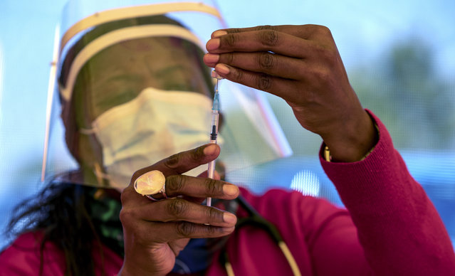 A health worker prepares a dose of the Pfizer coronavirus vaccine at the newly-opened mass vaccination program for the elderly at a drive-thru vaccination center outside Johannesburg, South Africa, Tuesday, May 25, 2021. South Africa aims to vaccinate 5 million of its older citizens by the end of June. (Photo by Themba Hadebe/AP Photo)