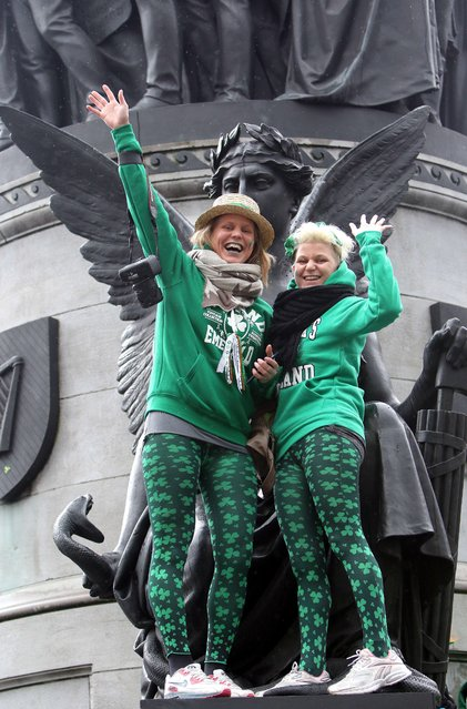 Spectators wave as they stand on the O'Connell Monument to watch the St Patrick's Day parade in Dublin on March 17, 2015. (Photo by Paul Faith/AFP Photo)
