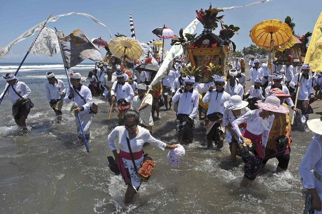 Balinese Hindus carry sacred objects as they walk along the shore during the Melasti ceremony ahead of Nyepi day at Pererenan Beach on the Indonesian island of Bali March 18, 2015 in this photo taken by Antara Foto. (Photo by Nyoman Budhiana/Reuters/Antara Foto)