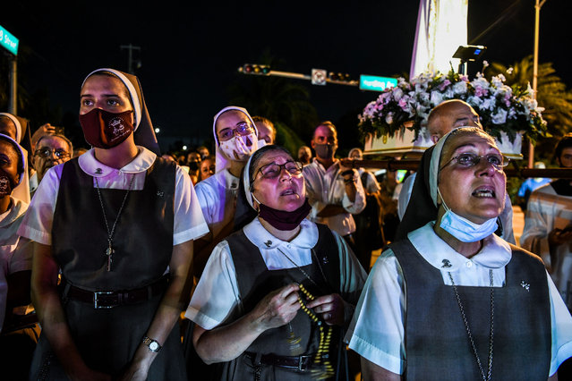 """Nuns from the St. Joseph's Catholic Church pray at the """"Surfside Wall of Hope & Memorial"""" near the site of the collapsed building in Surfside, Florida, north of Miami Beach, on July 7, 2021. Florida rescuers have made the """"extremely difficult decision"""" to end their search for survivors in the rubble of an apartment building which partially collapsed nearly two weeks ago, Miami-Dade county mayor Daniella Levine Cava said July 7. """"It is with deep profound sadness . that we made the extremely difficult decision to transition from operation search and rescue to recovery"""", Levine Cava told reporters in Surfside, near Miami, adding that the transition would formally take place at midnight. (Photo by Chandan Khanna/AFP Photo)"""