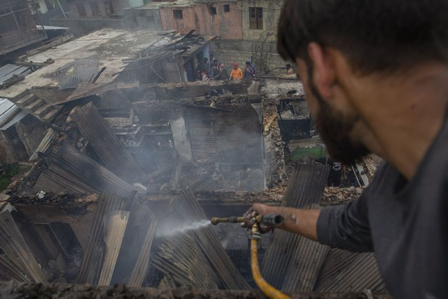 A Kashmiri villager sprays water on burning debris before clearing a house destroyed in a gunfight in Pulwama, south of Srinagar, Indian controlled Kashmir, Wednesday, July 14, 2021. (Photo by Dar Yasin/AP Photo)