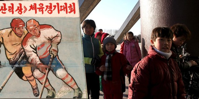 North Korean children walk past a standing signboard depicting ice hockey in Pyongyang, North Korea, in this undated handout picture. A Canadian man behind a series of trips to North Korea by basketball hall of famer Dennis Rodman is organising an ice hockey tournament that may draw former National Hockey League (NHL) players to the isolated country. (Photo by Michael Spavor/Reuters)