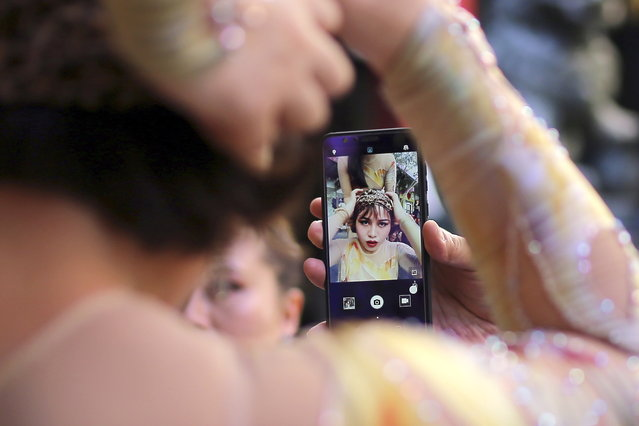 "A member of the Qinghai Acrobatic Troupe checks her hair with a smartphone during a media preview for the world premiere of cabaret show ""Shanghai Mimi"" as part of Sydney Festival in Chinatown, central Sydney, Australia, 08 January 2019. Sydney Festival 2019 runs from 09 to 27 January and will feature theatre, dance, circus, music, visual arts and talks from international and local artists. (Photo by Steven Saphore/EPA/EFE)"