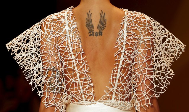 A tattoo is seen on the back of Brazilian top model Isabeli Fontana as she presents a creation from the Agua de Coco Summer 2016 Ready To Wear collection during Sao Paulo Fashion Week in Sao Paulo April 14, 2015. (Photo by Paulo Whitaker/Reuters)