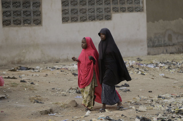 """Two young girls walk past a polling station following the presidential election being delayed by the Independent National Electoral Commission in Yola, Nigeria, Saturday, February 16, 2019. A civic group monitoring Nigeria's now-delayed election says the last-minute decision to postpone the vote a week until Feb. 23 """"has created needless tension and confusion in the country"""". (Photo by Sunday Alamba/AP Photo)"""