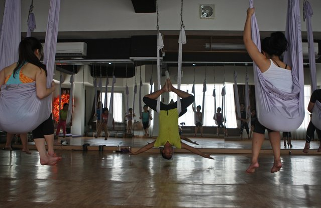 Yoga instructor Ari, center,  shows a yoga position using hammock during the Anti-Gravity yoga class at Svarga e-Motion Sanctuary at Dharmawangsa Square, Jakarta, Saturday, April 18, 2015. (Photo by Jurnasyanto Sukarno/JG Photo)