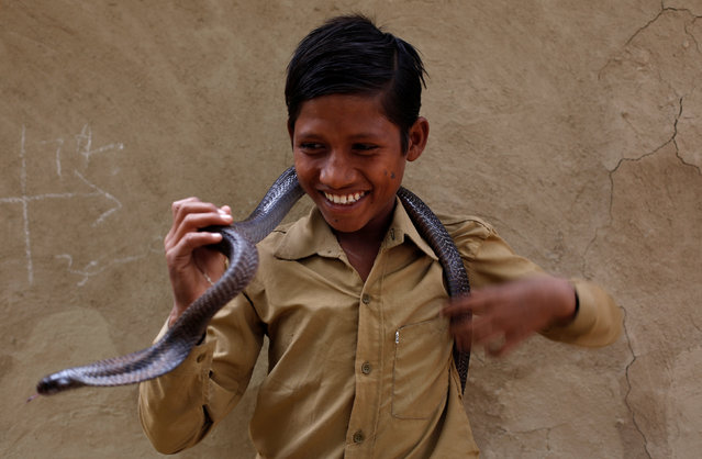 Rishi Nath poses for a photograph with a cobra snake in Jogi Dera (Snake charmers settlement), in the village Baghpur, in the central state of Uttar Pradesh, India November 10, 2016. (Photo by Adnan Abidi/Reuters)
