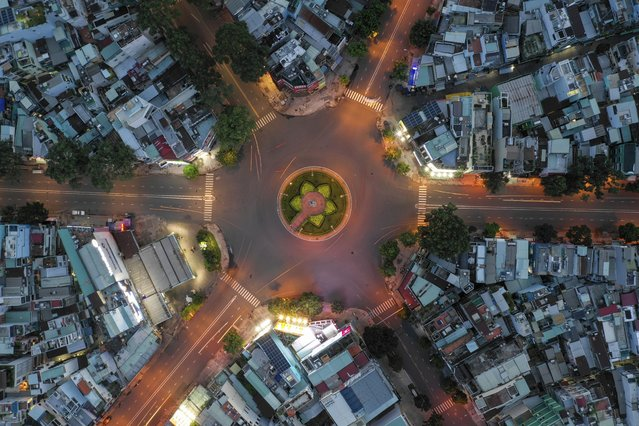 An empty intersection is seen from an aerial view in Ho Chi Minh City, Vietnam on July 22, 2021. Vietnam's southern metropolis Ho Chi Minh City has tightened restrictions with a curfew order starting from Monday evening to contain a surge of COVID-19. (Photo by Huu Khoa/AP Photo)