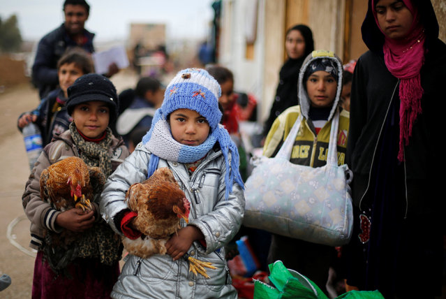 Displaced children who fled the Islamic State stronghold of the Arabi neighborhood, north of Mosul with their families carry their chickens as they wait to register their names at a military checkpoint before being transported to the camps in the east of Mosul, Iraq, January 25, 2017. (Photo by Muhammad Hamed/Reuters)
