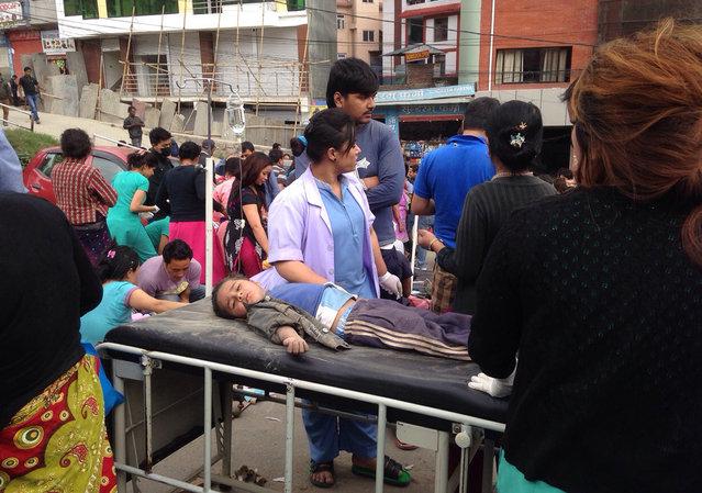 An injured child receives treatment outside Medicare Hospital in Kathmandu, Nepal, Saturday, April 25, 2015. (Photo by Niranjan Shrestha/AP Photo)