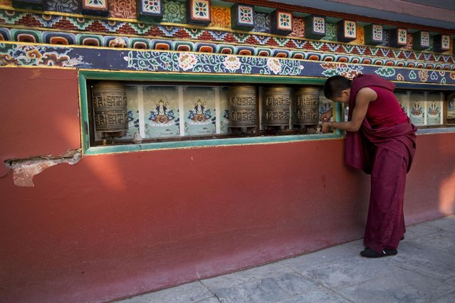 A Buddhist monk removes prayer wheels at the Shechen monastery that was partially damaged in Saturday's earthquake in Kathmandu, Nepal, Monday, April 27, 2015. (Photo by Bernat Armangue/AP Photo)