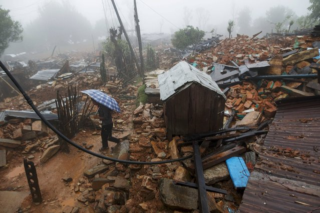 A man holds up a umbrella as he walks past a devastated area following Saturday's earthquake, at Paslang village in Gorkha, Nepal April 28, 2015. (Photo by Athit Perawongmetha/Reuters)
