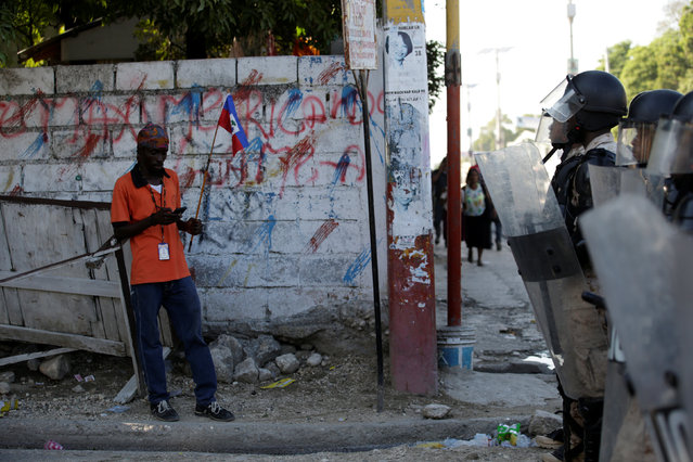 A protester uses his mobile phone while standing in front of a police line blocking a street during a demonstration against the results of the presidential election, in the streets of Port-au-Prince, Haiti, December 5, 2016. (Photo by Andres Martinez Casares/Reuters)