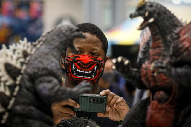 A man photographs merchandise during the 2021 New York Comic Con, at the Jacob Javits Convention Center in Manhattan in New York City, New York, U.S., October 7, 2021. (Photo by Brendan McDermid/Reuters)