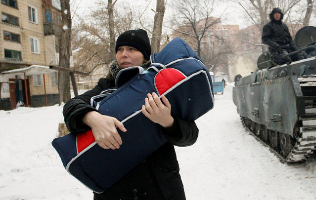 A woman carries a bag with a baby while being evacuated by local emergencies ministry members in Donetsk, Ukraine, February 2, 2017. (Photo by Alexander Ermochenko/Reuters)