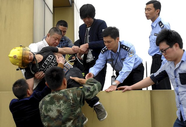 A man (in yellow helmet), who attempted to commit suicide, cries as he is taken to safety by rescuers on the roof of a 35-storey building, in Jinhua, Zhejiang province, China, April 24, 2015. The 30-year-old man, surnamed Wang, who works as a labour contractor in the city, attempted to kill himself due to a failed relationship. The authority managed to rescue him after talking to him about 50 minutes, local media reported. (Photo by Reuters/Stringer)
