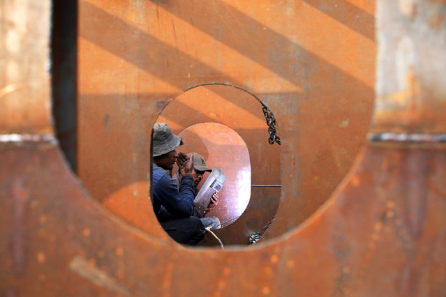 Workers weld iron sheets as they build a new ferry at a dockyard in Dhaka, Bangladesh, February 7, 2019. (Photo by Mohammad Ponir Hossain/Reuters)