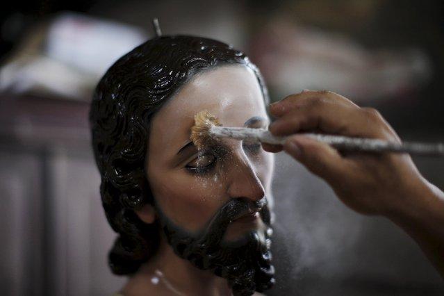 Jose Sabas Gomez applies talcum powder to a statue of El Jesus Nazareno in his workshop in Apastepeque, El Salvador March 9, 2016. (Photo by Jose Cabezas/Reuters)