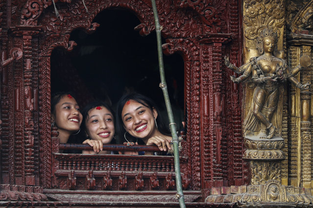 A former living goddess Kumari, center, watches Indra Jatra festival in Kathmandu, Nepal, Sunday, September 19, 2021.Tens of thousands of devotees packed the old palace courtyard in the heart of Nepal's capital to celebrate Indra Jatra festival Sunday which marks the start of the festival season in the Himalayan nation. (Photo by Niranjan Shrestha/AP Photo)